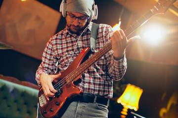 Focused Caucasian musician playing bass guitar with earphones on ears. Full length.