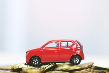 Little toy red car over a lot of money stacked coins. for  bank loans costs finance. insurance, buying car finance concept. buy and pay by installments down payment a car.