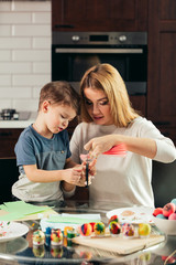 Happy young mother spending time with her son of preschool age, sitting at kitchen table with a lot of colored paper and painted eggs. Easter preparations are in full swing. oncept of parenthood.