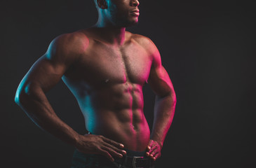 Close shot of athletic African well built man with six pack abs posing shirtless at studio over dark background.