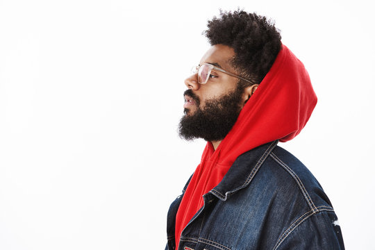 Profile shot of cool and stylish confident and self-satisfied african american male rap-singer wearing hoodie and denim jacket looking with raised chin left being self-assured over gray background