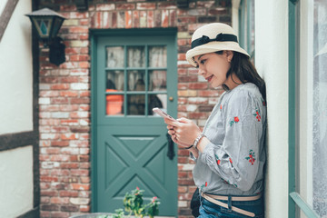 Beautiful teenager student girl using smart phone leaning against plain red stone texture brick wall networking and smiling outdoors. Adolescent technology lifestyle. vintage asian woman happy stand