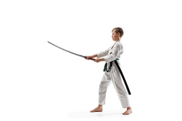 Teen boy fighting at Aikido training in martial arts school. Healthy lifestyle and sports concept. Fightrer in white kimono on white background. Karate man with concentrated face in uniform.