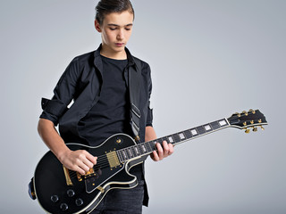 Fifteen years old guitarist with a  black electric guitar. Teenage musician holds guitar