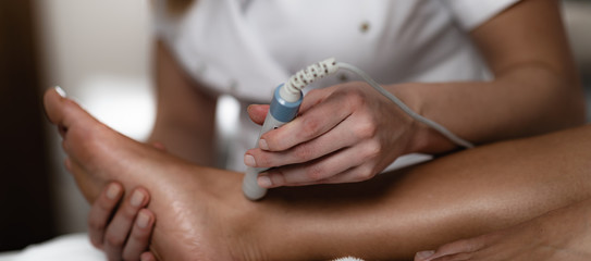 Laser therapy. Physical therapist treating patient's ankle joint