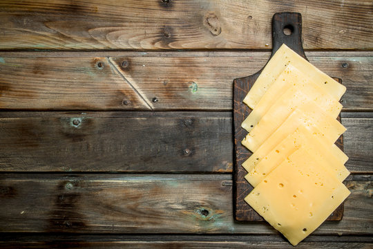 Thin slices of cheese on the cutting Board.