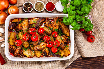 Grilled chicken wings with baked potatoes and vegetables
