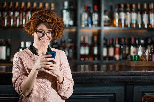 Red-haired female with short curly hair using mobile phone while enjoying night in bar with shelves of alcohol