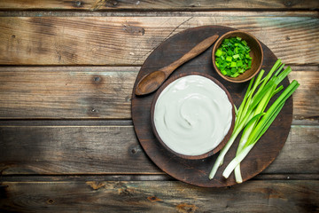 Fresh sour cream in bowl with green onions .