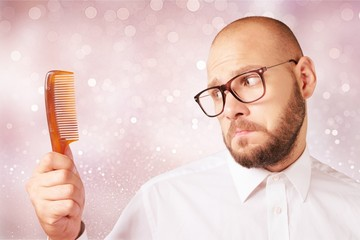 Adult bald  man hand holding comb