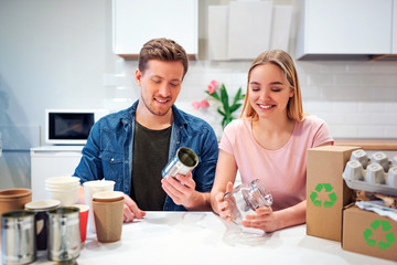 Protect the environment. Young couple recycling metal tin can and glass while sitting at the table with other waste at home