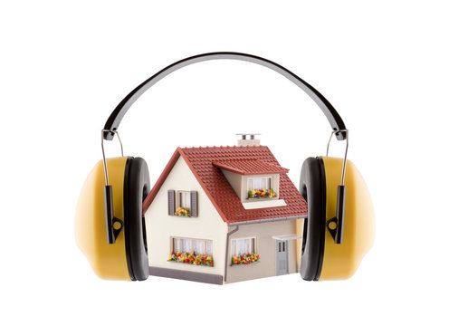 Protection against noise. Hearing protection yellow ear muffs with house miniature isolated on white background