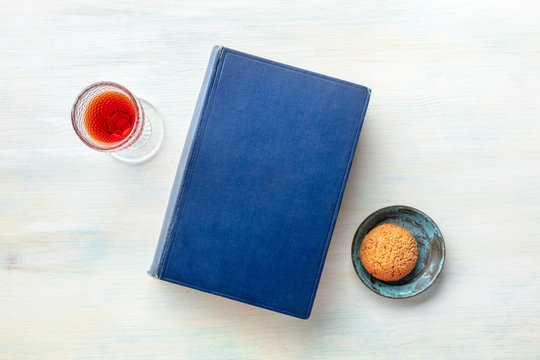 An old book with a glass of dessert wine and a biscuit, shot from above with a place for text