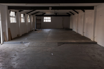 The inside of an empty farm building with white walls and black beams