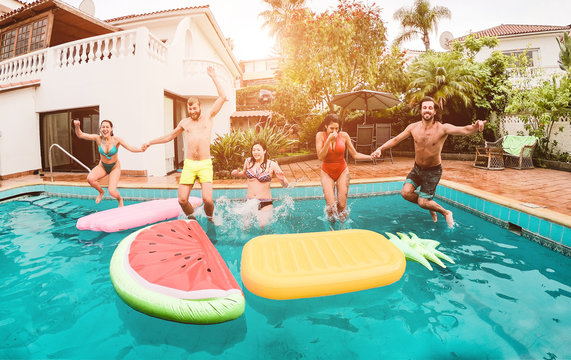 Group of happy friends drinking jumping in pool at sunset party - Main focus on guys faces