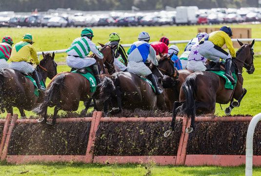 View of race horses and jockeys jumping a race track hurdle from behind