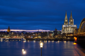 Kölner Dom und Groß St. Martin Kirche mit Blick auf die Hohenzollernbrücke und die Kölner Altstadt und den Fischmarkt während Sonnenuntergang , Blaue Stunde