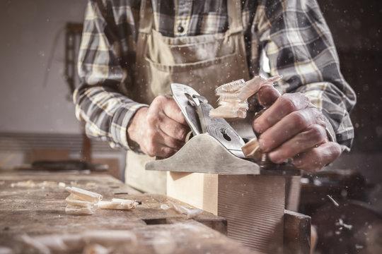 Hände eines Tischlers bei der Arbeit mit dem Hobel