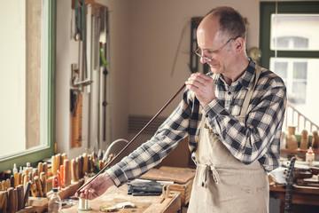 Geigenbauer überprüft einen Bogen per Augenmaß
