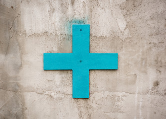 Blue plus sign for decoration on the concrete wall outdoors