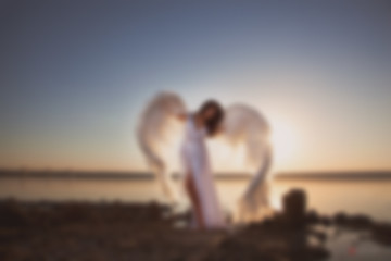 Blurry picture for background, Angel at sunset by the sea,  good idea fantasy.