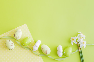 Flat lay composition with white daffodils and easter eggs on a green background