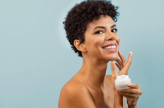Young brazilian woman applying moisturizer