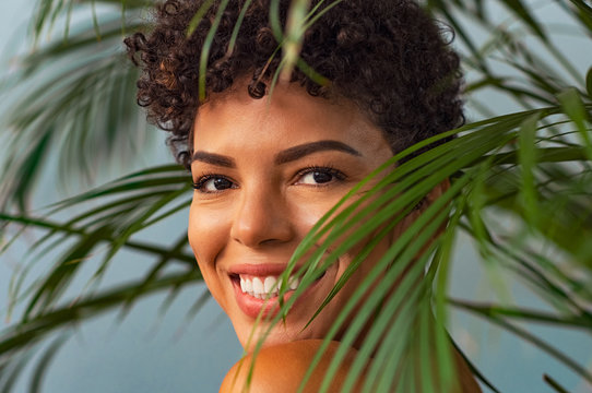Beauty young woman smiling through palm leaves