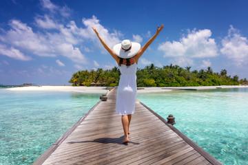 Glückliche Frau in weißem Sommerkleid läuft über einen Holzsteg auf den Malediven und genießt ihren tropischen Uraub