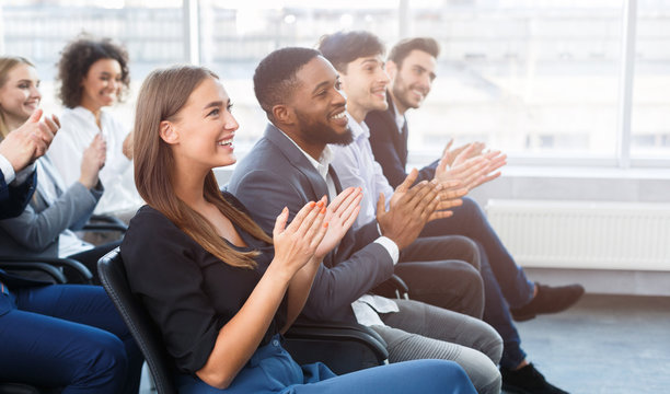 Business seminar. Colleagues clapping hands in office