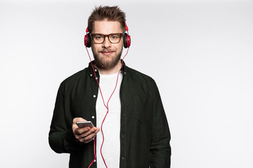 Studio portrait of gorgeous bearded male fashionably dressed in trendy clothes posing on white background. Lovely young man with mobile phone in hands. Technology concept