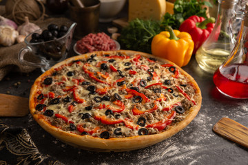 Pizza with minced meat, paprika and olives for the restaurant menu.