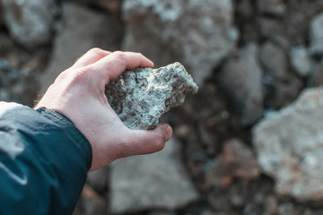 Male hand holding a stone.