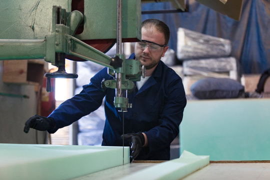 Young man in a furniture factory is cutting the foam for the sofa