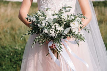 wedding bouquet of white flowers with ribbons in the hands of the bride