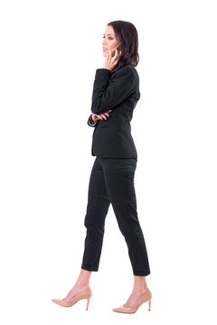 Side view of busy business woman walking and communicating on cellphone. Full body isolated on white background.