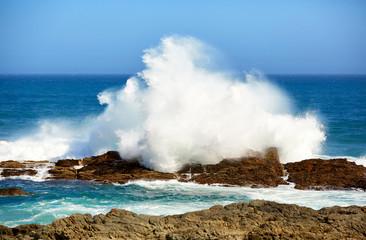 Huge wave breaks on rocky coast