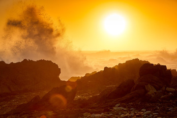 Huge wave breaks on rocky coast at sunset