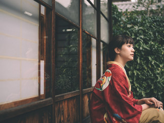 Side view of thoughtful young woman in kimono sitting outdoors