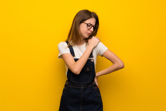 Woman over yellow wall suffering from pain in shoulder for having made an effort