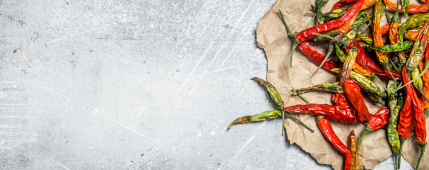 Dried hot pepper pods on paper.