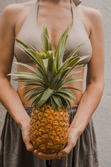 woman in boho clothes keep the tropical fruit pineapple in hands on the light background in Bali