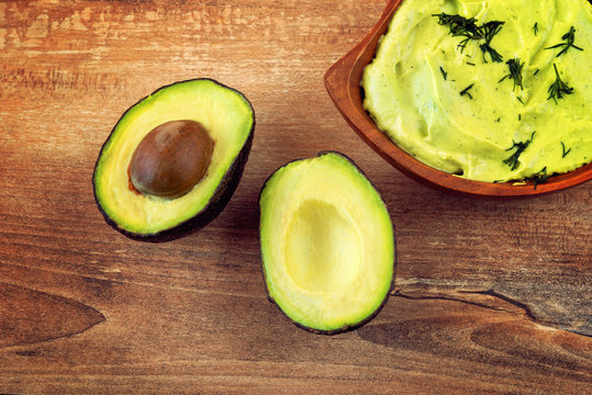 Fresh avocado cream in brown bowl and fresh sliced avocados on brown wooden background. Top view. Copy space. Vegetarian food concept, vintage style, avocado background.