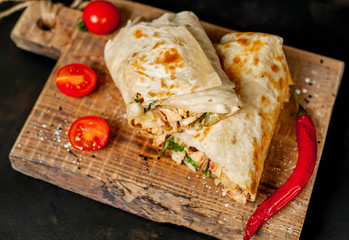 Photo sur Aluminium Snack Burrito wraps with chicken and vegetables on a cutting board, against a background of concrete, Mexican shawarma