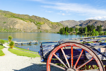old cart with red wooden spoked wheel and Lake Dunstan New Zealand.