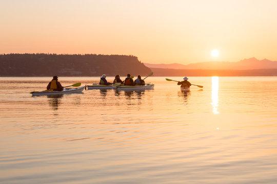 Group of people men and women in kayaks sea kayaking. Active outdoor adventure water sports enjoying beautiful nature at sunrise.