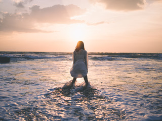Rear view of woman standing in sea during sunset