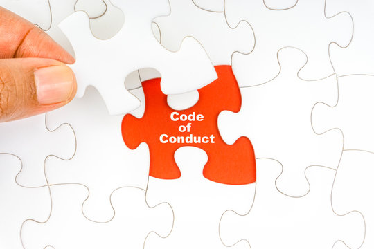 Hand holding piece of jigsaw puzzle with word CODE OF CONDUCT. Selective focus