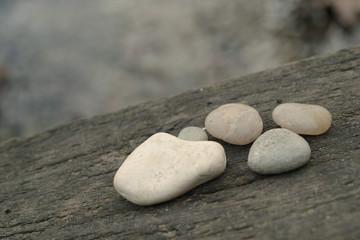 Zen pebbles on wooden bridge by waterside