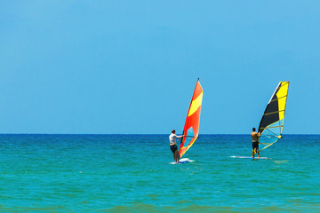 Windsurfing on the background of the sea landscape and clear sky.Two windsurfers men go in for sports, copy space.